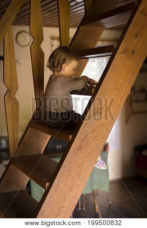 The child sits on the wooden stairs in the cottage and draws there
