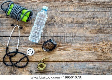 Fitness for loosing weight. Jump rope, measure tape and water on wooden background top view.