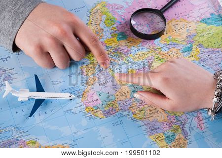 Couple planning airplane trip to Tunisia, point on map, top view
