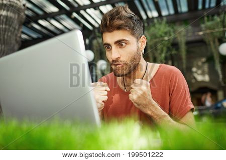Shot of worrying focused man with stylish hairstyle dressed casually closely looking at the screen of his notebook, watching online translation of match, clenching his fists in nerves.