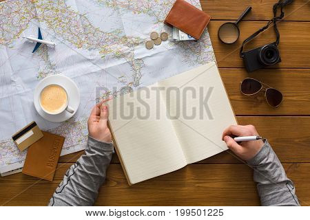 Travel planning concept top view. Taking notes to notebook on map background, search for best trip, copy space for text