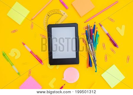 back to school or office styed pattern with e-book and multicolored school supplies on yellow