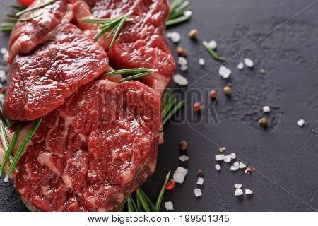 Raw rib eye steak with herbs and spices closeup. Cooking ingredients for healthy restaurant meals. Fresh meat, pepper salt and rosemary on black stone background with copy space