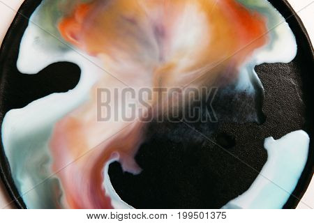 Abstract image of colorful streaks of liquid on black background. Watercolor blots of milk with gradient orange paint flowing each other