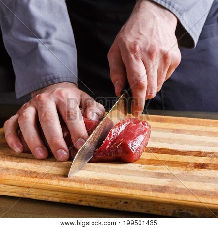 Man cutting filet mignon on wooden board at restaurant kitchen. Chef preparing fresh meat for cooking. Modern cuisine backgroung with copy space