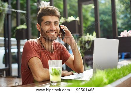 Shot of male smiling to the camera good-looking freelancer working online via laptop at the cafe, discussing work on the cell phone. Bearded guy in red t-shirt sitting in front of notebook sitting at wooden table and drinking lemonade.