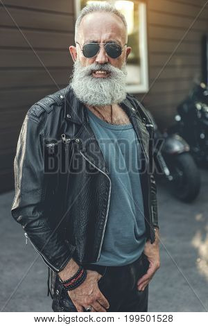 Happy old biker in sunglasses is standing near motorbikes. He wearing leather jacket and looking at camera with bright smile. Portrait