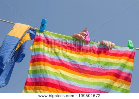 woman hanging towel to dry on clothesline after laundry in the sun on blur nature background good weather at summer or spring season saving energy. Clean laundry is hung up by a woman to dry