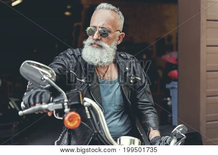 Serious elder biker in goggles is taking handles of motorcycle and looking aside with concentrated face. He wearing jacket made of leather. Portrait