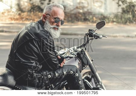 Elder bearded biker in goggles is sitting on motorbike and wearing leather trousers with rivets. He turning back to camera. Portrait