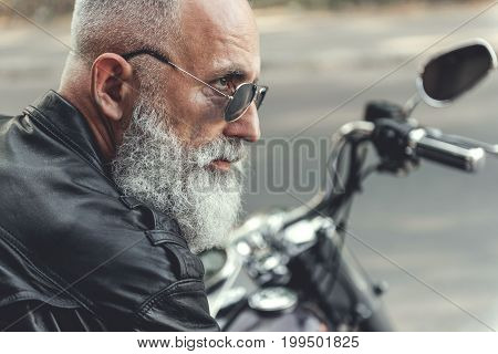 Experienced aged bearded biker wearing jacket made of leather. He is looking ahead with interest. Profile