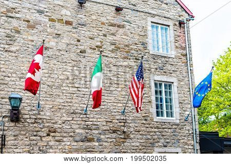 Flags of European and North American countries hanging off building including Canadian United States Italian and European Union