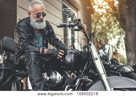 Busy elder bearded biker is sitting on motorcycle and putting hand on fuel tank. He wearing clothes made of black leather