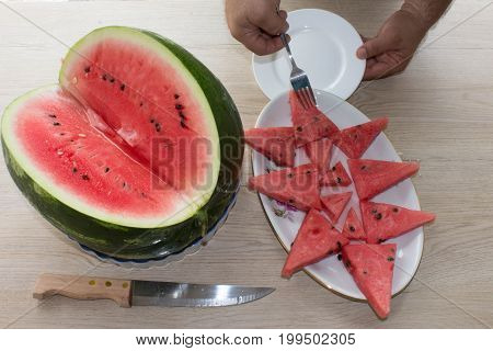 Ripe watermelons on table on wooden background. High angle view of sliced watermelon