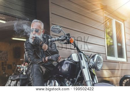 Old bearded biker in sunglasses is sitting on motorcycle and whiffing cigar. He wearing leather clothes. Low angle
