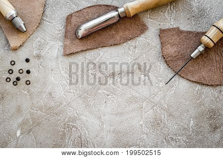 Leather craft tools on grey stone background top view.