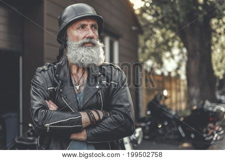Thoughtful old bearded biker wearing black helmet. He crossing hands and looking aside with curiosity. Portrait. Copy space