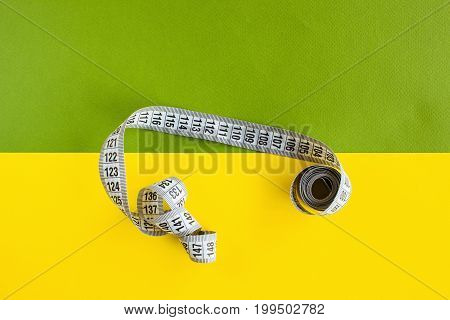 Tape measure on colorful green and yellow background. Battle of the bulge, dieting, balanced nutrition concept, top view with free space