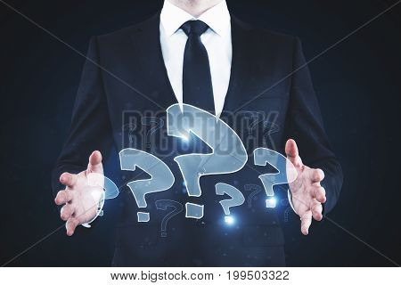 Businessman holding abstract drawn question marks on blue background. FAQ concept