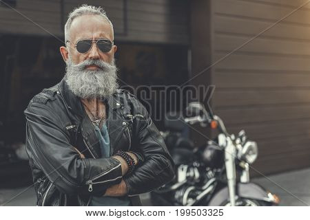 Attentive mature bearded biker is standing afore motorbike and crossing arms. He wearing black leather jacket. Portrait. Copy space