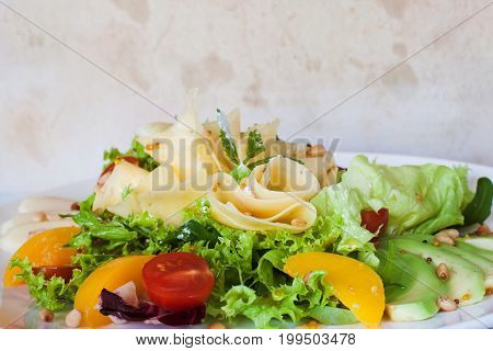 Green salad with cheese and fruits on plate. Lettuce, fresh vegetables decorated pine nuts, avocado and pearch, dirty grey background, close up