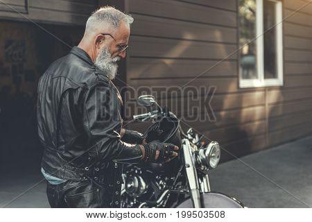 Confident mature bearded biker is going to wear black helmet. He is standing near motorbike. Copy space on right side