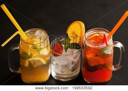 Close up fresh cocktails on black background for satisfying thirst. Orange and strawberry cold drink in jar and glass with ice decorated mint and sliced citrus, refreshment in hot weather