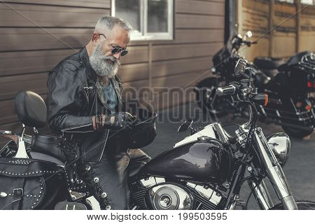 Concentrated matured biker is sitting on motorcycle and holding black helmet. He locating near building