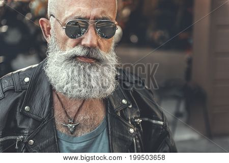 Assured old spectacled biker is wearing black jacket made of leather. He glancing ahead. Portrait. Copy space