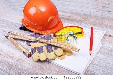 Orange hard hat, safety glasses, gloves and measuring tape on wooden background