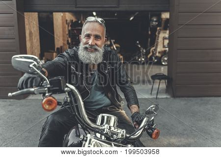 Cheerful mature bearded biker is sitting on motorcycle and holding handles. He looking at camera with bright smile. Portrait. Copy space