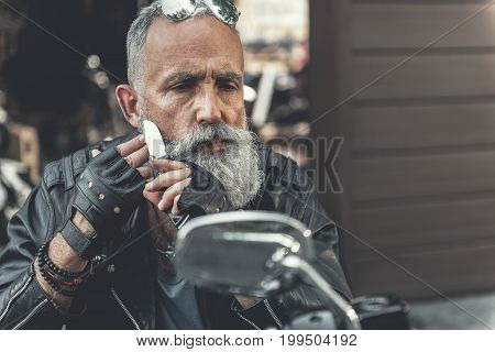 Attentive mature biker is sitting on motorcycle and using his knife in order to shave cheek. He looking at mirror with determination. Portrait. Copy space on right side