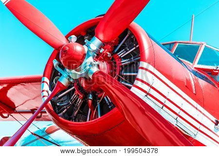 Red retro propeller engine airplane against blue sky
