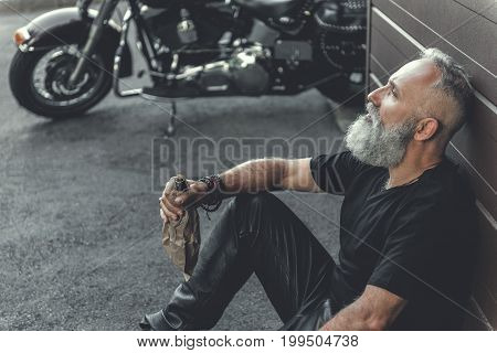 Tired mature bearded biker is leaning against wall and holding bottle with alcohol. He sitting near motorbike. Top view
