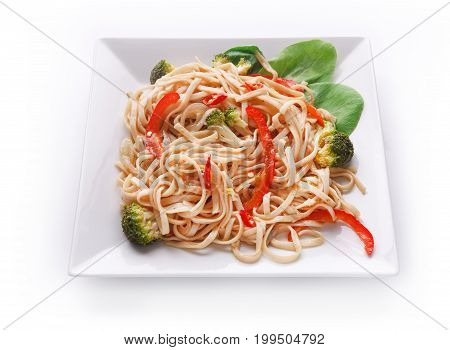 Asian food plate isolated at white background. Vegetarian stir fry with noodles served on square platter and green spinach leaves decoration
