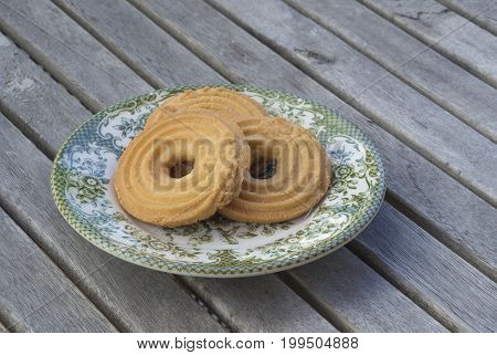 crispy butter cookies biscuits on green painted plate on wooden desk background