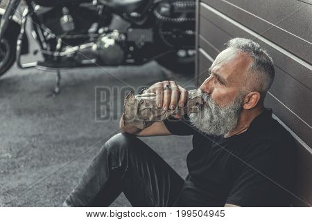 Mature bearded biker is leaning against wall and drinking alcohol beverage. Motorbike is near him. Portrait