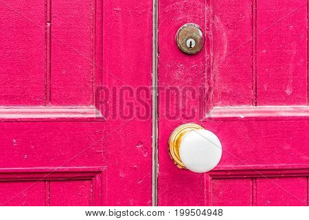 Closeup Of White Door Knob Handle And Red, Magenta Painted Wooden Door