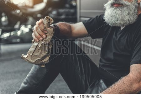 Elder gray-haired biker is sitting near wall. He going to drink alcohol. Focus on beverage in male hand. Close up
