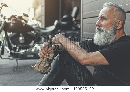 Tired aged bearded biker is leaning against wall and looking ahead with bewilderment. He holding bottle with alcohol. Portrait. Copy space on left side