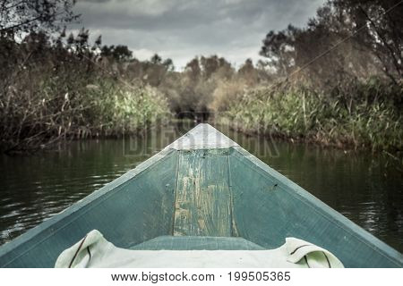 Bow of boat with forward direction towards bank on river in overcast day with dramatic sky symbolizing way forward