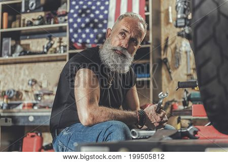 Assured elder bearded biker is going to repair his vehicle. He sitting in workshop and looking aside with expectation. Portrait
