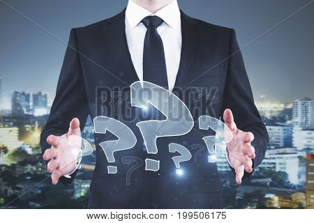 Businessman holding abstract drawn question marks on night city background. Confused concept