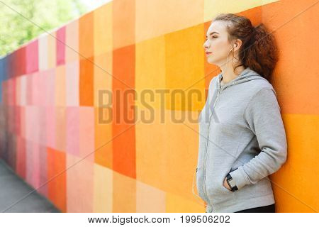 Pensive redhead woman leaning on bright graffiti wall, relaxing from jog training, copy space