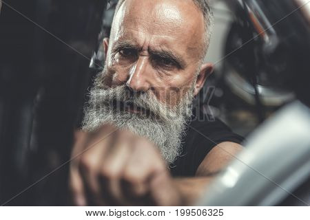 Confident mature bearded biker is repairing his motorbike. Focus on male concentrated face. Portrait. Close up