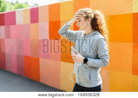 Tired sporty woman having headache after hard training, touching her forehead, copy space