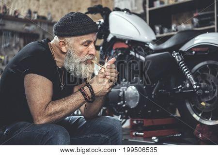 Mature bearded biker is setting fire to cigarette. He sitting near modern motorcycle in garage