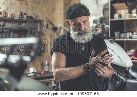 Busy mature bearded biker is locating in garage. He using black rag in order to make arms clean