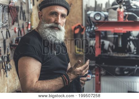 Confident mature bearded biker is standing in garage and glancing at camera with wistfulness. He holding small rag. Portrait. Copy space on right side