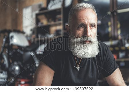 Serious old bearded biker is glancing ahead with expectation. Portrait. Copy space on left side